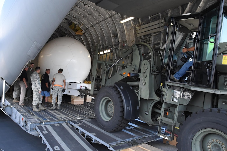 Crew members unload the Low Profile Antenna off the C-17 Globemaster III ramp after the 4th Space Operations Squadron mobile flight lands in Hawaii. The safe handling of the massive assets requires meticulous preparation and coordination between different agencies. (U.S. Air Force photo/2nd Lt. Darren Domingo)