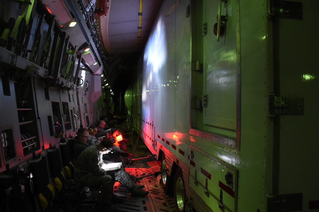 The 4th Space Operations Squadron mobile team rests on the outskirts of the Advanced Ground Mobile space operating semitrailer aboard a C-17 Globemaster III during a flight to their Hawaii operating location. The AGM needed to be tightly and safely secured with chains and homemade wooden support dunnage for the overseas flight. (U.S. Air Force photo/2nd Lt. Darren Domingo)