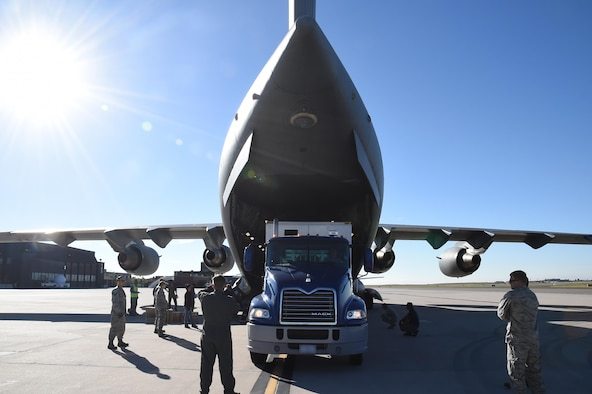 A loadmaster directs the Advanced Ground Mobile driver onto the ramp of a C-17 Globemaster III. During the loading process, skilled drivers must maneuver the AGM within an accuracy area of just a few inches, taking care not to damage the plane or semitrailer. (U.S. Air Force photo/2nd Lt. Darren Domingo)