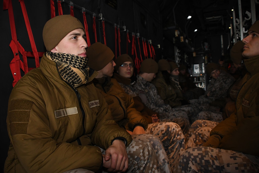 Latvian air force members sit in the cargo area of a C-130H from Dobbins Air Reserve Base, Ga., while parked on the runway at Lielvarde Air Base, Latvia, during Sky Fist, Oct. 6, 2016. Sky Fist was a bilateral, aircraft mishap training exercise designed to strengthen the partnership between the U.S. and Latvia. (U.S. Air Force photo by Staff Sgt. Alan Abernethy)