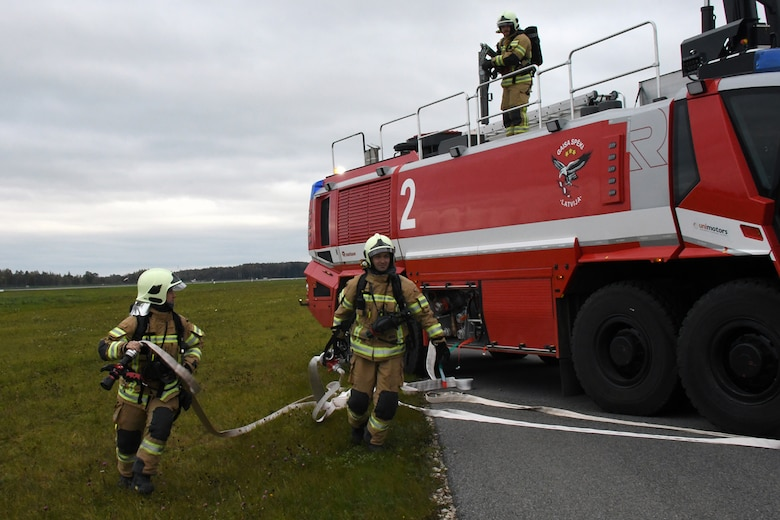 Latvian fire and rescue emergency responders arrive on the runway at Lielvarde Air Base, Latvia, where a C-130 from Dobbins Air Reserve Base, Ga. is positioned in a simulated crash during Sky Fist, Oct. 6, 2016. Sky Fist was a bilateral aircraft mishap training exercise designed to strengthen the partnership between the U.S. and Latvia. (U.S. Air Force photo by Staff Sgt. Alan Abernethy)