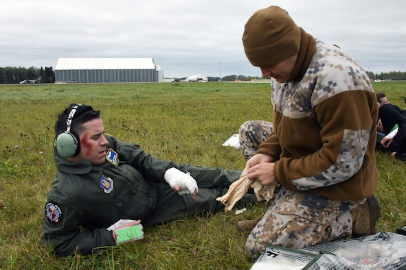 Senior Airman Joshua Stubbs, 700th Airlift Squadron loadmaster, receives simulated medical treatment from a Latvian air force medical technician during Sky Fist, an aircraft mishap training exercise, held at Lielvarde Air Base, Latvia, Oct. 6, 2016. Sky Fist was a bilateral exercise designed to strengthen the partnership between the U.S. and Latvia. (U.S. Air Force photo by Staff Sgt. Alan Abernethy)