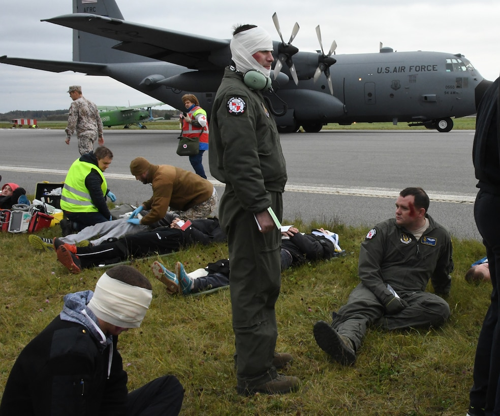 Senior Airman Joshua Stubbs, 700th Airlift Squadron loadmaster, and 1st Lt. Brian Reed, 700th AS pilot, join others with simulated injuries during Sky Fist, an aircraft mishap training exercise, held at Lielvarde Air Base, Latvia, Oct. 6, 2016. Sky Fist was a bilateral exercise designed to strengthen interoperability and the partnership between the U.S. and Latvia. (U.S. Air Force photo by Staff Sgt. Alan Abernethy)