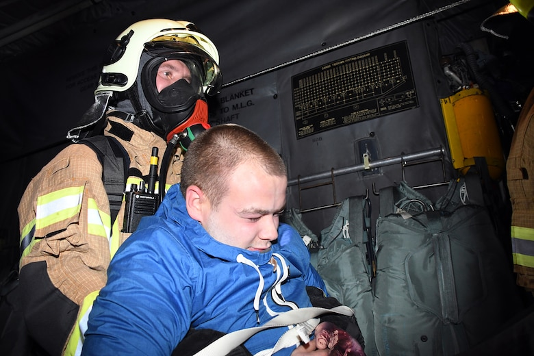 A Latvian fire and rescue emergency responder evacuates an exercise participant from a 94th Airlift Wing C-130H positioned on the runway in a simulated crash at Lielvarde Air Base, Latvia, during Sky Fist, Oct. 6, 2016. Sky Fist was a bilateral, aircraft mishap training exercise designed to strengthen the partnership between the U.S. and Latvia. (U.S. Air Force photo by Staff Sgt. Alan Abernethy)