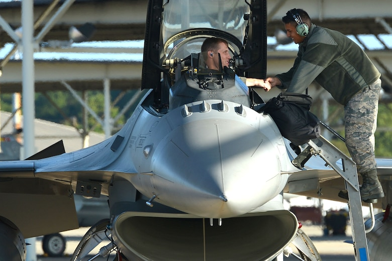 An F-16CM Fighting Falcon pilot assigned to the 20th Fighter Wing shakes hands with a tactical aircraft maintainer assigned to the 20th Aircraft Maintenance Squadron during an aircraft evacuation at Shaw Air Force Base, S.C., Oct. 6, 2016. Forty-eight F-16s were evacuated from Shaw in anticipation of Hurricane Matthew, which hit South Carolina as a Category 2 hurricane. (U.S. Air Force photo by Airman 1st Class Christopher Maldonado)