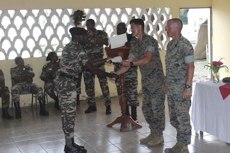 1st Lt. William Anderson, a team commander, and Gunnery Sgt. Fredrick Volz, a staff non-commissioned officer with Special Purpose Marine Air-Ground Task Force Crisis Response-Africa, congratulate a Cameroonian soldier with Forces Fusiliers Marins et Palmeurs Commando during graduation in Limbé, Cameroon, Sept. 23, 2016. Marines trained on small unit tactics, weapons handling, orders processing and detainee handling with the FORFUMAPCO soldiers to combat illicit trafficking in the region.  (U.S. Marine Corps courtesy photo/released)