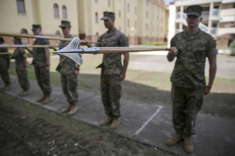 Marines with Special Purpose Marine Air-Ground Task Force Crisis Response-Africa practice guidon manual during Corporals Course at Naval Air Station Sigonella, Italy, September 16, 2016.  Thirty-five Marines with SPMAGTF-CR-AF completed the three-week course which included classes on land navigation, sword and guidon manual, fire team and squad formations, and included opportunities to develop the NCO's mentoring and leadership skills.  (U.S. Marine Corps photo by Cpl. Alexander Mitchell/released)