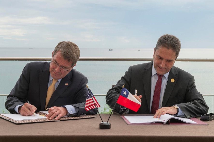 Defense Secretary Ash Carter signs an agreement with Chilean National Defense Minister Jose Gomez during the Conference of Defense Ministers of the Americas.