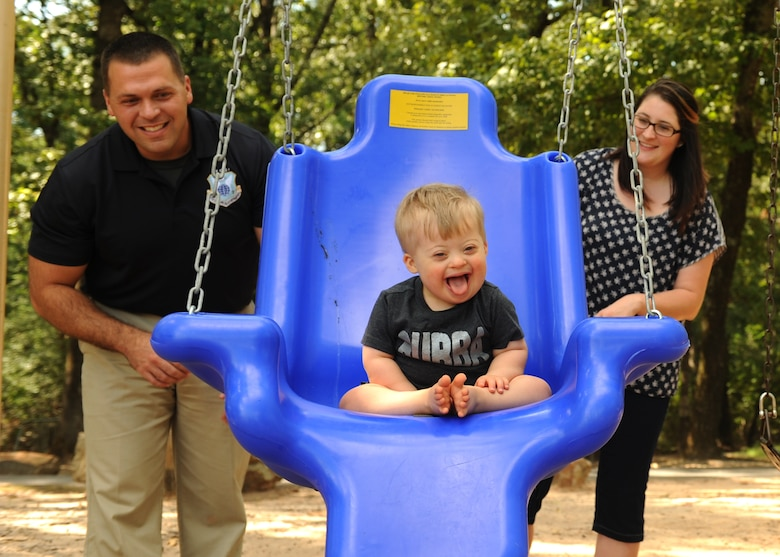 U.S. Air Force Special Agent Adam Boccher and Brittany Boccher push their son, Blake, in a swing, Sept. 9, 2016, at Little Rock Air Force Base, Ark. The accessible therapeutic swing was unveiled at the playground near the Family Camp and small base lake by the base Exceptional Family Member Program.