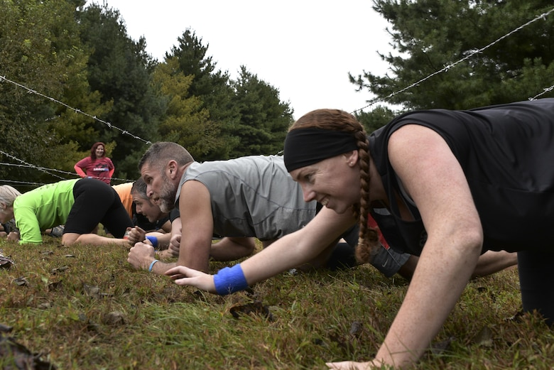 Meghan Root, 70th Intelligence, Surveillance and Reconnaissance Wing Sexual Assault Response Coordinator, low-crawls under barbed wire during the 2016 Savage Race October 8, 2016 at Kennedyville, Md. 70th ISRW participants endured a seven-mile obstacle course of cargo net walls, creeks, ice cold water and climbing to test their stamina and strength as a team. (U.S. Air Force photo/Staff Sgt. Alexandre Montes)