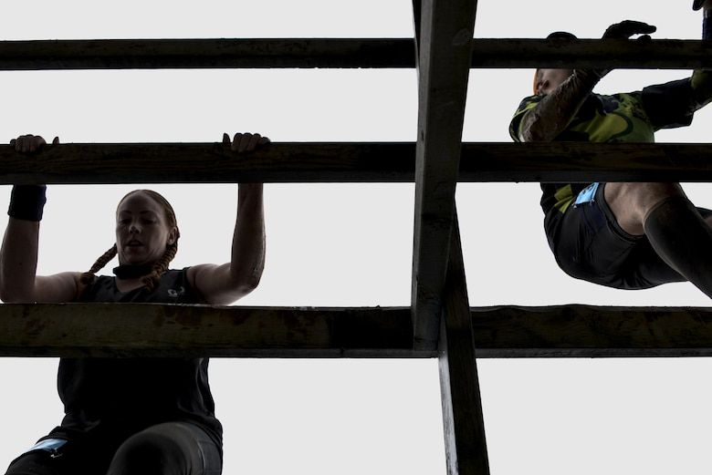Meghan Root, 70th Intelligence, Surveillance and Reconnaissance Wing Sexual Assault Response Coordinator, climbs a wooden fence obstacle in the 2016 Savage Race October 8, 2016 at Kennedyville, Md. 70th ISRW participants endured a seven-mile obstacle course of cargo net walls, creeks, ice cold water and climbing to test their stamina and strength as a team. (U.S. Air Force photo/Staff Sgt. Alexandre Montes)