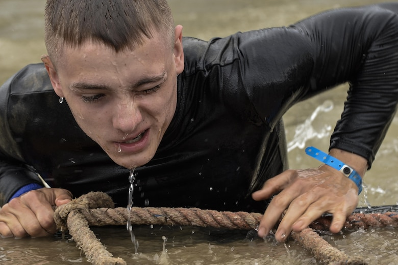 Jackson Hensley climbs out of 'Davey Jones' Locker', a 15 foot drop to a 15 foot deep pool obstacle during the 2016 Savage Race October 8, 2016 at Kennedyville, Md. 70th ISRW participants endured a seven-mile obstacle course of cargo net walls, creeks, ice cold water and climbing to test their stamina and strength as a team. (U.S. Air Force photo/Staff Sgt. Alexandre Montes)