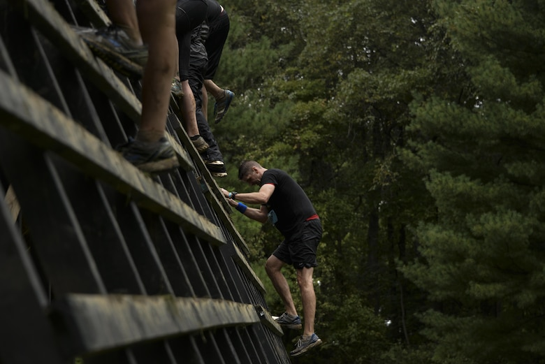 Col. Gregory Gillinger, 70th Intelligence, Surveillance and Reconnaissance Wing vice commander, climbs up a wooden ladder during the 2016 Savage Race October 8, 2016 at Kennedyville, Md. 70th ISRW participants endured a seven-mile obstacle course of cargo net walls, creeks, ice cold water and climbing to test their stamina and strength as a team. (U.S. Air Force photo/Staff Sgt. Alexandre Montes)