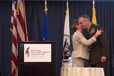 Ellyn Dunford kisses her husband, Chairman of the Joint Chiefs of Staff Marine Corps Gen. Joseph F. Dunford Jr., after introducing him to speak at the 2016 National Military Family Association Leadership Luncheon in Arlington, Va., Oct. 11, 2016. DoD photo by D. Myles Cullen