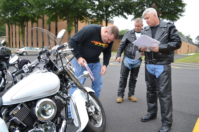 (Left to right) Sgt. 1st Class Eric Baker, Sgt. 1st Class David Mangan and Maj. Stephen Yarber, of the 80th Training Command (TASS), conduct motorcycle safety checks at the command's Family Programs Center in Richmond, Va., as they prepare for the motorcycle mentorship ride in honor of Sgt. Scott McGinnis on Oct. 6, 2016. McGinnis, 22, died in a motorcycle accident July 4, 2016 in Centre, Ala., where he was struck by another vehicle.