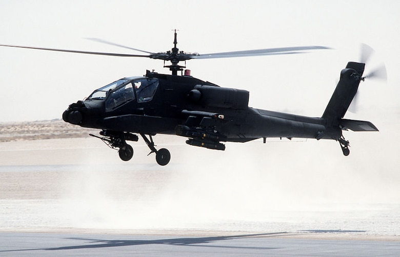 AH-64 Apache helicopter taking off from air base.