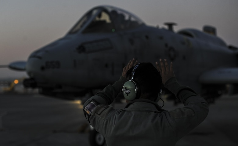 Senior Airman Scott Martinez, 355th Aircraft Maintenance Squadron crew chief, Davis-Monthan Air Force Base, Ariz., signals to an A-10 Thunderbolt II as the pilot taxis down the runway at Nellis Air Force Base, Nev., Oct. 4, 2016. The 357th Fighter Squadron is participating in a realistic air-land integration combat training exercise involving air forces of the U. S. and its allies. (U.S. Air Force photo by Airman 1st Class Kevin Tanenbaum/Released)