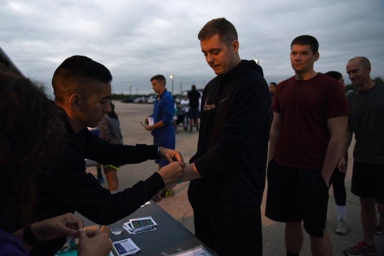 U.S. Air Force 2nd Lt. Ryan Davis, 315th Training Squadron student, signs in for the annual Sexual Assault Prevention and Response Color Run near the Kiowa Trail on Goodfellow Air Force Base, Texas, Oct. 8, 2016. The SAPR office gave the participants free white t-shirts for the run in order to spread sexual assault awareness. (U.S. Air Force photo by Airman 1st Class Caelynn Ferguson/Released)