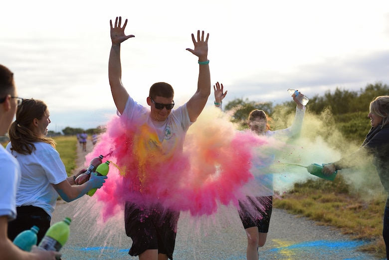 Participants during the annual Sexual Assault Prevention and Response Color Run jog through a cloud of powder color on the Kiowa Trail on Goodfellow Air Force Base, Texas, Oct. 8, 2016. Volunteers were stationed along the trail to throw colors at the participants as they ran by. (U.S. Air Force photo by Airman 1st Class Caelynn Ferguson/Released)