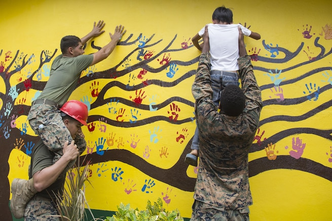 Marines and students put handprints on an elementary school wall restored during Philippine Amphibious Landing Exercise 33 in Cagayan Valley, Philippines, Oct. 10, 2016. The Marines are assigned to Bravo Company, 9th Engineer Support Battalion, 3rd Marine Logistics Group, 3rd Marine Expeditionary Force. Marine Corps photo by Cpl. Allison Lotz