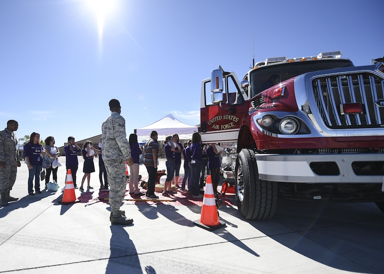 Fire Fighters from the 49th Civil Engineer squadron show children a fire truck during the fourth annual New Mexico Aviation Aerospace Association Career Expo Oct. 6, 2016 at Holloman Air Force Base N.M. About 2,500 middle school through college-level students from across New Mexico came out to learn about the science, technology, engineering and mathematics fields. The goal of STEM is to motivate and educate students by giving them a taste of what aviation and aerospace engineering is all about. These STEM events also get the students talking to people who are working directly in STEM industries.  (U.S. Air Force photo by Staff Sgt. Stacy Jonsgaard)