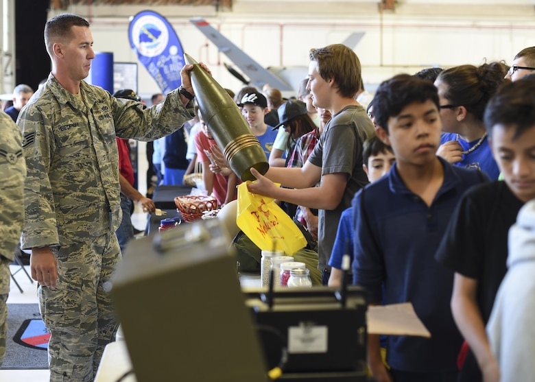 Staff Sgt. Evan Dieckhoff, Explosive Ordnance Disposal technician with 49th Civil Engineer squadron hands a a plastic training aid a mock-up of an artillery projectile to a student during the fourth annual New Mexico Aviation Aerospace Association Career Expo Oct. 6, 2016 at Holloman Air Force Base N.M. About 2,500 middle school through college-level students from across New Mexico came out to learn about the science, technology, engineering and mathematics fields. The goal of STEM is to motivate and educate students by giving them a taste of what aviation and aerospace engineering is all about. These STEM events also get the students talking to people who are working directly in STEM industries.  (U.S. Air Force photo by Staff Sgt. Stacy Jonsgaard)