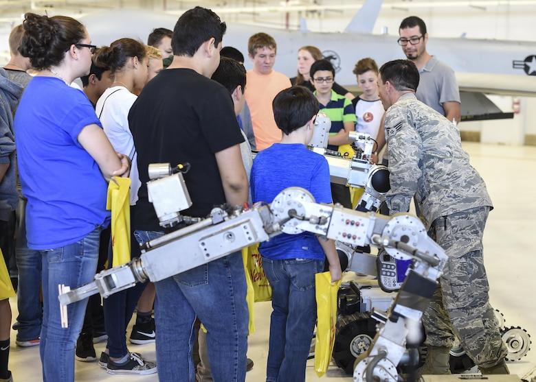 Senior Airman Kevin Oseguera Explosive Ordnance Disposal technician with 49th Civil Engineer squadron demonstrates how what a bomb disposal robot is used for during the fourth annual New Mexico Aviation Aerospace Association Career Expo Oct. 6, 2016 at Holloman Air Force Base N.M. About 2,500 middle school through college-level students from across New Mexico came out to learn about the science, technology, engineering and mathematics fields. The goal of STEM is to motivate and educate students by giving them a taste of what aviation and aerospace engineering is all about. These STEM events also get the students talking to people who are working directly in STEM industries.  (U.S. Air Force photo by Staff Sgt. Stacy Jonsgaard