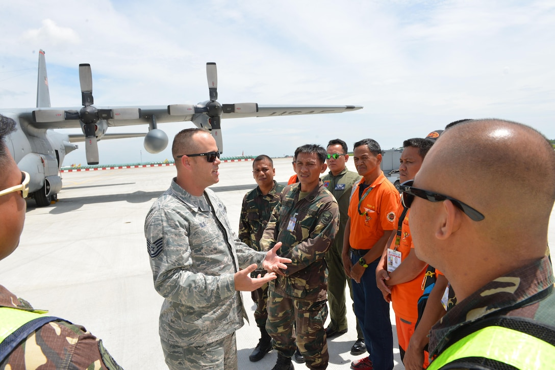 U.S. Air Force Tech. Sgt. Devon Blue (left), 18th Expeditionary Airlift Squadron fire protection specialist, facilitates discussion on flight line firefighting operations with members of the Philippine Air Force and Philippine Federal Aviation Administration firefighters next to a U.S. Air Force C-130 Hercules during a subject matter expert exchange as part of the current iteration of U.S. Pacific Command's Air Contingent at Brigadier General Benito N Ebuen Air Base, Lapu-Lapu City, Philippines, Sept. 26, 2016. The Air Contingent is helping build the capacity of the Philippine Air Force and increases joint training, promotes interoperability and provides greater and more transparent air and maritime situational awareness to ensure safety for military and civilian activities in international waters and airspace. Its missions include air and maritime domain awareness, personnel recovery, combating piracy, and assuring access to the air and maritime domains in accordance with international law. (U.S. Air Force photo by Capt. Mark Lazane)