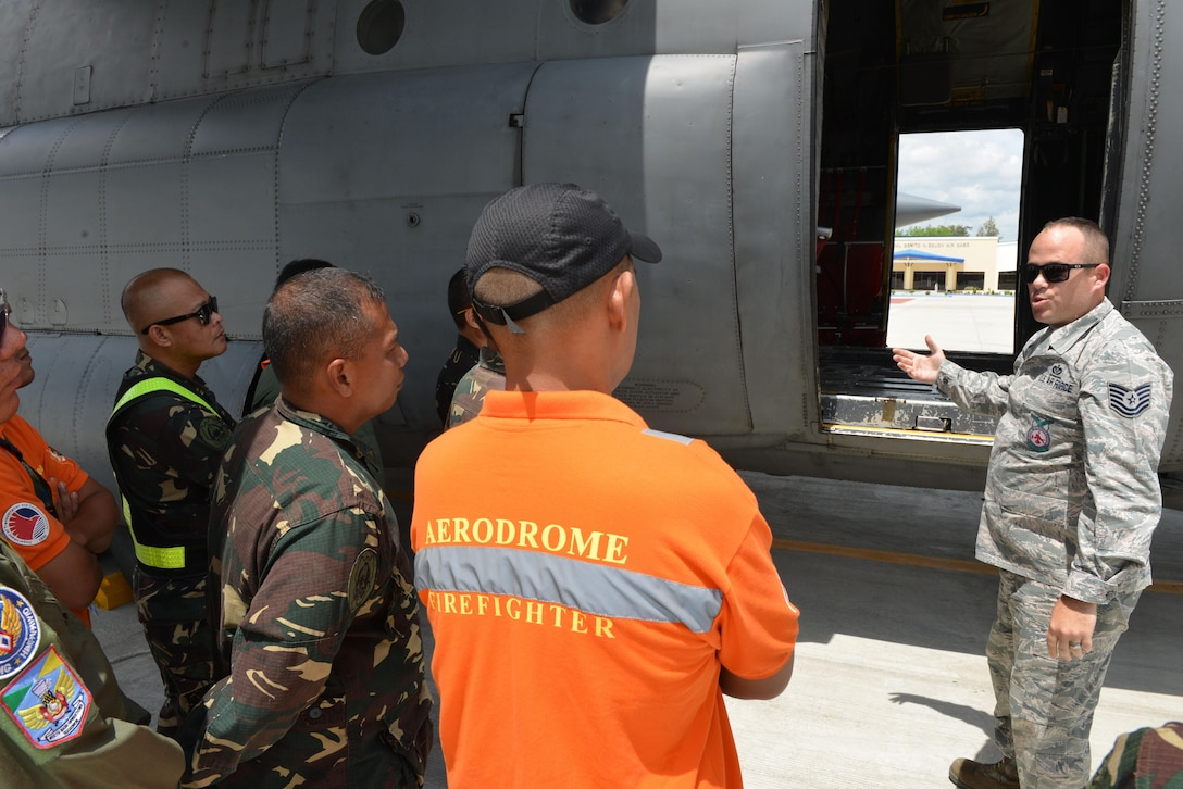 U.S. Air Force Tech. Sgt. Devon Blue, 18th Expeditionary Airlift Squadron fire protection noncommissioned officer in charge, facilitates discussion on flight line firefighting operations with members of the Philippine Air Force and Philippine Federal Aviation Administration firefighters next to a U.S. Air Force C-130 Hercules during a subject matter expert exchange as part of the current iteration of U.S. Pacific Command's Air Contingent at Brigadier General Benito N Ebuen Air Base, Lapu-Lapu City, Philippines, Sept. 26, 2016. The Air Contingent is helping build the capacity of the Philippine Air Force and increases joint training, promotes interoperability and provides greater and more transparent air and maritime situational awareness to ensure safety for military and civilian activities in international waters and airspace. Its missions include air and maritime domain awareness, personnel recovery, combating piracy, and assuring access to the air and maritime domains in accordance with international law. (U.S. Air Force photo by Capt. Mark Lazane)