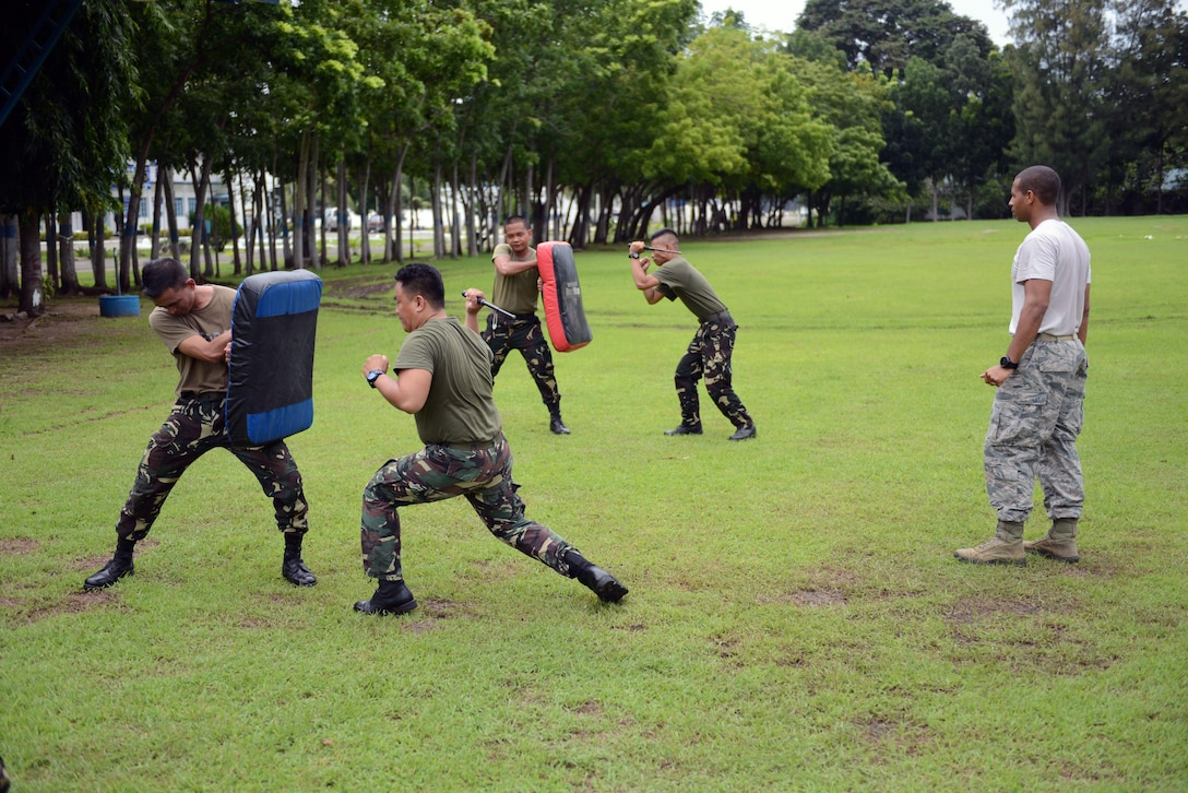 U.S. Air Force Staff Sgt. Antoine Dunlap (right), 18th Expeditionary Airlift Squadron security forces member, observes baton practice with his Philippine Air Force counterparts during a subject matter expert exchange as part of the current iteration of U.S. Pacific Command's Air Contingent at Brigadier General Benito N Ebuen Air Base, Lapu-Lapu City, Philippines, Oct. 4, 2016. The Air Contingent is helping build the capacity of the Philippine Air Force and increases joint training, promotes interoperability and provides greater and more transparent air and maritime situational awareness to ensure safety for military and civilian activities in international waters and airspace. Its missions include air and maritime domain awareness, personnel recovery, combating piracy, and assuring access to the air and maritime domains in accordance with international law. (U.S. Air Force photo by Capt. Mark Lazane)