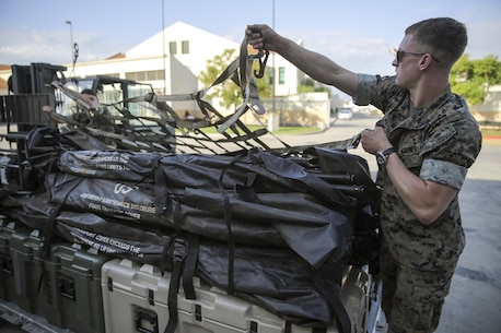 Cpl. Jeffrey Whitehouse, a landing support specialist with Special Purpose Marine Air-Ground Task Force Crisis Response-Africa, covers gear on a pallet with a securing net at Naval Air Station Sigonella, Italy, Oct. 6, 2016. Landing support specialists deployed with SPMAGTF-CR-AF have supported 187 flights containing 817,635 pounds of gear and 2,750 personnel, aboard nine different aircrafts. (U.S. Marine Corps photo taken by Cpl. Alexander Mitchell/released)