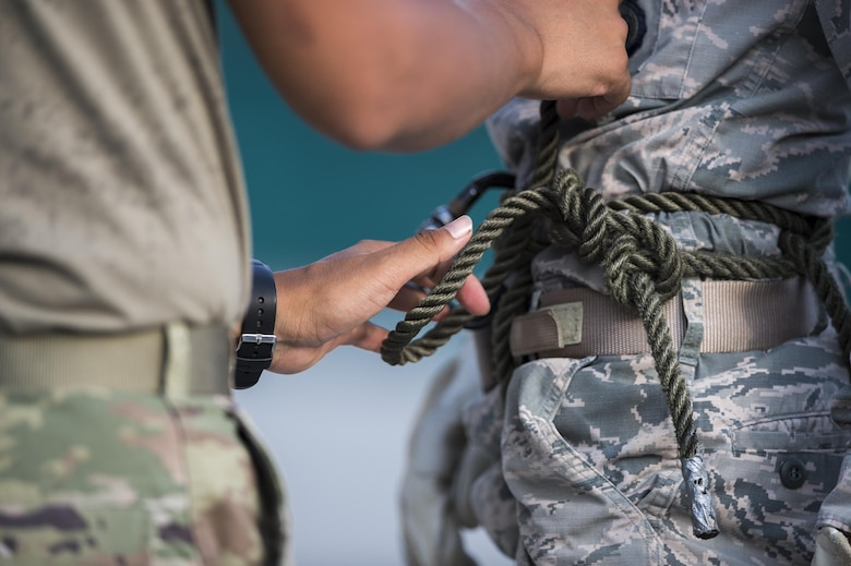 Tech. Sgt. Jose DeLeon, 820th Combat Operations Squadron NCO in charge of deployed radio frequency systems, checks a 105th Base Defense Squadron member's harness during rappel training, Sept. 29, 2016, at Moody Air Force Base, Ga. The 820th Base Defense Group was able to use its post-deployment experience and training resources to help train the Air National Guardsmen of the 105th BDS. (U.S. Air Force photo by Tech. Sgt. Zachary Wolf)