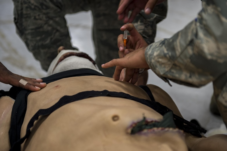 Airman 1st Class Gerardo Balsa, 105th Base Defense Squadron security forces member, demonstrates how to perform a needle decompression on the chest during tactical combat casualty care training, Sept. 29, 2016, at Moody Air Force Base, Ga. Tactical combat casualty care tests and reinforces participants' lifesaving medical skills while they are in high-stress, combat scenarios. (U.S. Air Force photo by Tech. Sgt. Zachary Wolf)