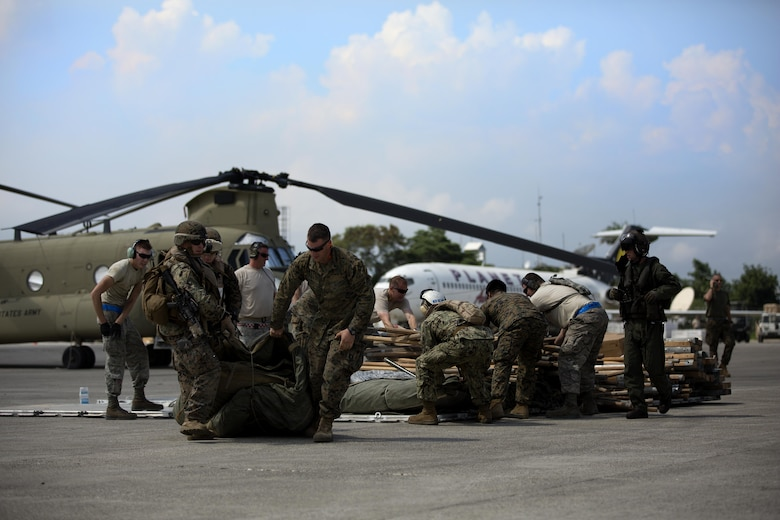 U.S. military members load relief supplies onto a CH-53E super stallion helicopter during a disaster relief mission at Port-au-Prince, Haiti, Oct. 10, 2016. The 24th MEU is part of a larger U.S. response to the government of Haiti request for humanitarian assistance. The U.S. effort is coordinated by the Department of State and the U.S. Agency for International Development. (U.S. Marine Corps photo by Lance Cpl. Melanye E. Martinez)