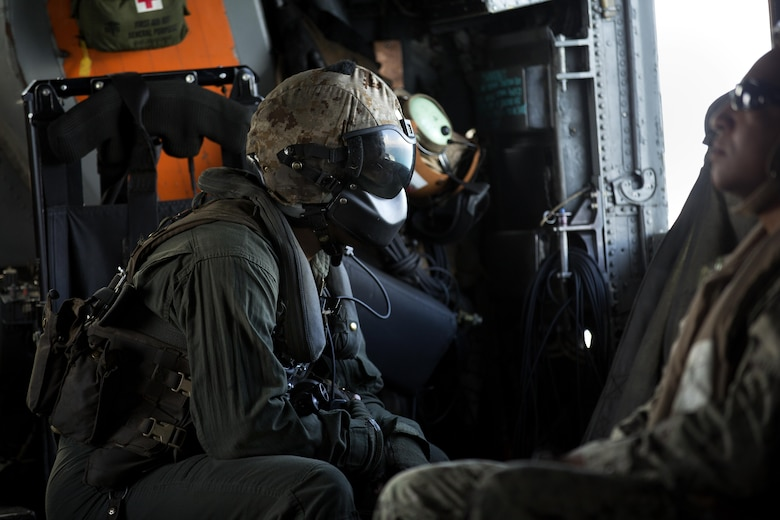 A U.S. Marine with Marine Medium Tiltrotor Squadron 365, 24th Marine Expeditionary Unit (24th MEU), looks out from a CH-53E super stallion helicopter during a disaster relief mission at Port-au-Prince, Haiti, Oct. 10, 2016. The 24th MEU is part of a larger U.S. response to the government of Haiti request for humanitarian assistance. The U.S. effort is coordinated by the Department of State and the U.S. Agency for International Development. (U.S. Marine Corps photo by Lance Cpl. Melanye E. Martinez)
