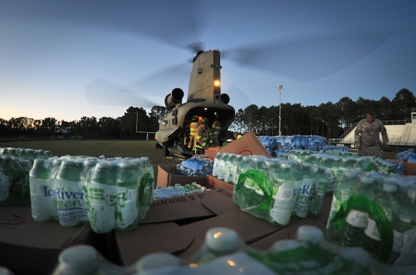 A South Carolina National Guard's CH-47F Chinook helicopter assigned lands at the Whale Branch Early College High School and delivers water and food supplies to the community of Seabrook in the aftermath of Hurricane Matthew Oct. 9. DLA Troop Support provided meals for 6,000 Marine recruits who were evacuated before the storm from Paris Island, South Carolina to Albany, Georgia. Hurricane Matthew peaked as a Category 4 hurricane in the Caribbean and hit the S.C. coast on Oct. 7.
