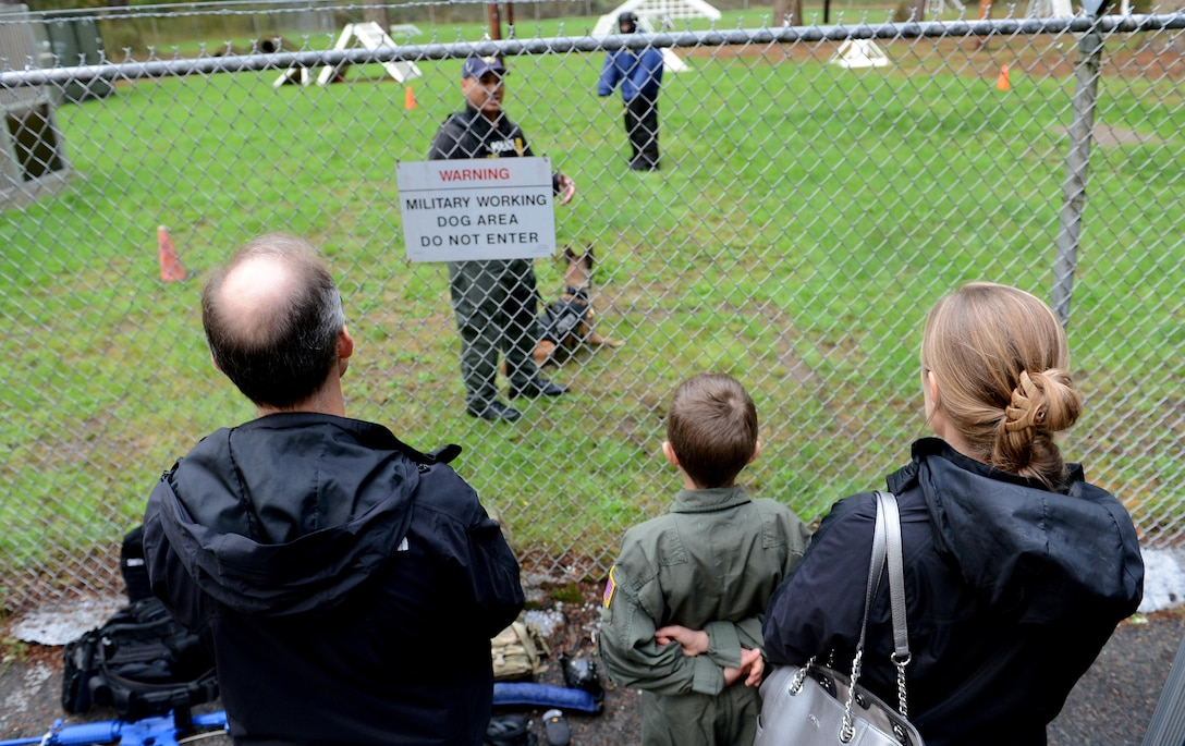 Ben Lambertson (middle) and his parents Paul (left) and Michelle (right), watch a Military Working Dog demo during his Pilot for a Day visit Oct. 7, 2016 at Joint Base Lewis-McChord, Wash. While at the MWD demo, Ben and his family had a chance to interact with the canines, and observe working dogs doing some obedience training and bite work. (U.S. Air Force photo/Senior Airman Divine Cox)