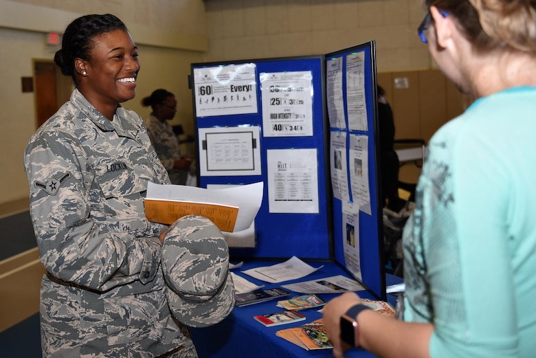 U.S. Air Force Airman Kelsey Locklin, 315th Training Squadron student, speaks to a representative during the Volunteer Fair at Carswell Fieldhouse on Goodfellow Air Force Base, Texas, Oct. 12, 2016. Locklin viewed a display for health, fitness and nutrition facts and references. (U.S. Air Force photo by Airman 1st Class Caelynn Ferguson/Released)