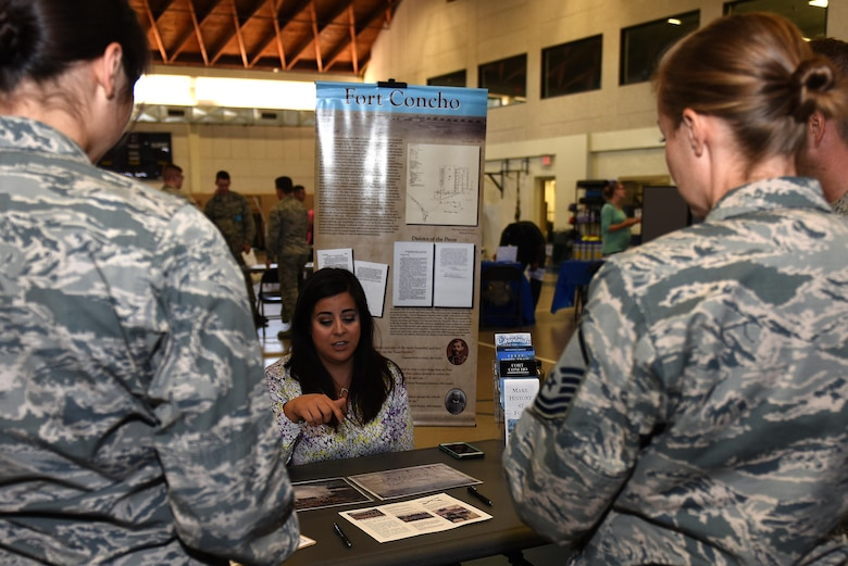Airmen learn about Fort Concho events and volunteer opportunities at the Volunteer Fair at Carswell Fieldhouse on Goodfellow Air Force Base, Texas, Oct. 12, 2016. The Fort Concho display included events such as Halloween murder mysteries and ghost tours. (U.S. Air Force photo by Airman 1st Class Caelynn Ferguson/Released)
