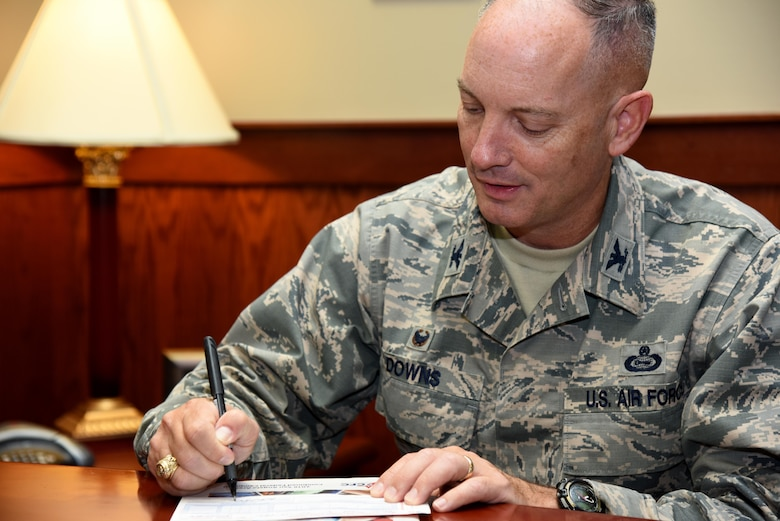 U.S. Air Force Col. Michael Downs, 17th Training Wing Commander, signs a Combined Federal Campaign donation sheet in his office at the Norma Brown building on Goodfellow Air Force Base, Texas, Oct. 11, 2016. The CFC is running now until Dec. 15. (U.S. Air Force photo by Senior Airman Joshua Edwards/Released)