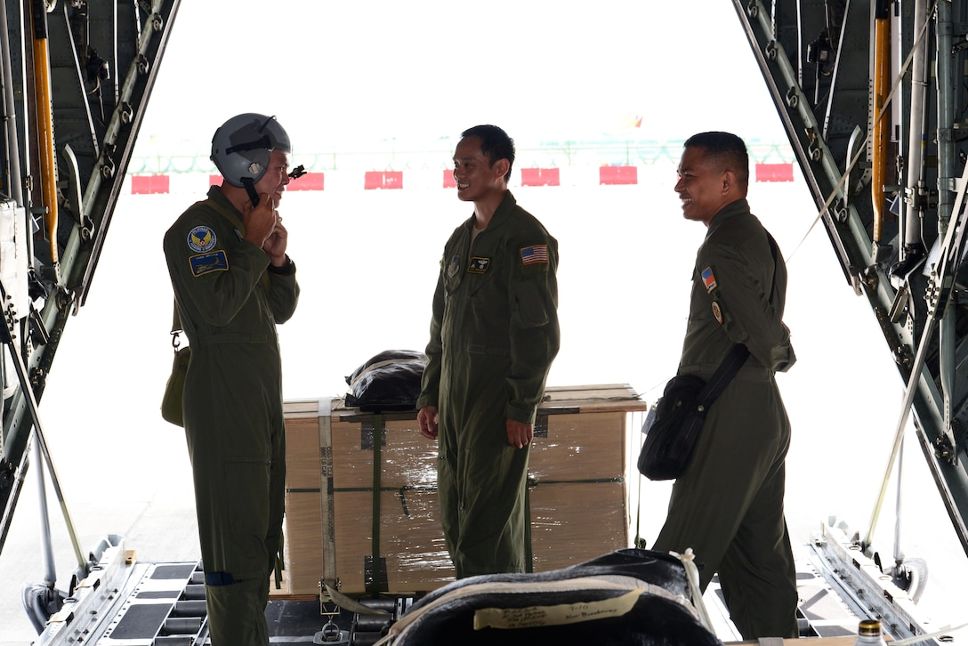 Philippine Air Force C-130 crew members prepare a U.S. Air Force C-130 Hercules aircraft for low-cost, low-altitude airdrop operations with U.S. Air Force Tech. Sgt. John Quiason (middle), 36th Airlift Squadron, 374th Airlift Wing, Yokota Air Base, Japan, during the current iteration of a rotational Air Contingent at Brigadier General Benito N Ebuen Air Base, Lapu-Lapu City, Philippines, Oct. 5, 2016. For the exchange, Yokota-based C-130s flew with members of the Philippine Air Force's 220th Airlift Wing, from Brig. Gen. Benito N. Ebuen Air Base, Lapu-Lapu City, Philippines, and discussed the intricacies of LCLA bundle drops. Two Yokota-based C-130s and crews, members of the 36th Contingency Response Group, Andersen Air Force Base, Guam, and other units from across U.S. Pacific Command conducted bilateral training missions and subject matter expert exchanges alongside their Philippine Air Force counterparts. The Air Contingent is helping build the capacity of the Philippine Air Force and increases joint training, promotes interoperability and provides greater and more transparent air and maritime situational awareness to ensure safety for military and civilian activities in international waters and airspace. Its missions include air and maritime domain awareness, personnel recovery, combating piracy, and assuring access to the air and maritime domains in accordance with international law. (U.S. Air Force photo by Capt. Mark Lazane)