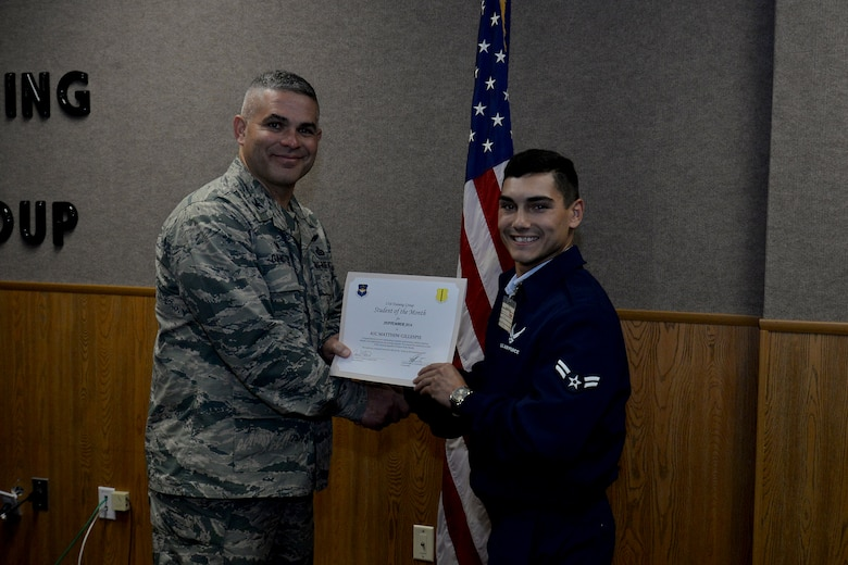 U.S. Air Force Col. Alex Ganster, 17th Training Group Commander, presents the 315th Training Squadron Enlisted Student of the Month award for September 2016 to Airman 1st Class Matthew Gillespie at Brandenburg Hall on Goodfellow Air Force Base, Texas, Oct. 7, 2016. (U.S. Air Force photo by Airman 1st Class Randall Moose/Released)