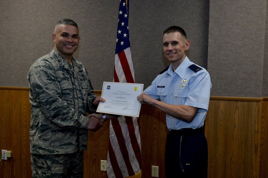 U.S. Air Force Col. Alex Ganster, 17th Training Group Commander, presents the 315th Training Squadron Officer Student of the Month award for September 2016 to 2nd Lt. Skyler Conklin at Brandenburg Hall on Goodfellow Air Force Base, Texas, Oct. 7, 2016. (U.S. Air Force photo by Airman 1st Class Randall Moose/Released)