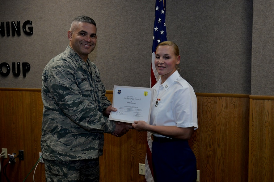 U.S. Air Force Col. Alex Ganster, 17th Training Group Commander, presents the 312th Training Squadron Student of the Month award for September 2016 to U.S. Army Pfc. Regina Giudice at Brandenburg Hall on Goodfellow Air Force Base, Texas, Oct. 7, 2016. (U.S. Air Force photo by Airman 1st Class Randall Moose/Released)