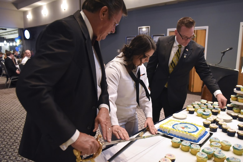 U.S. Navy Retired Master Chief Petty Officer Sean Lemmons, Petty Officer 3rd Class Caitlin Snow, Center for Information Warfare Training Detachment Goodfellow student and retired Master Chief Petty Officer Jerry Marlett cut the Navy's 241st birthday cake at the Event Center on Goodfellow Air Force Base, Texas, Oct. 7, 2016. The cutting of the cake by the oldest and youngest sailor is a long held tradition. (U.S. Air Force photo by Airman 1st Class Chase Sousa/Released)