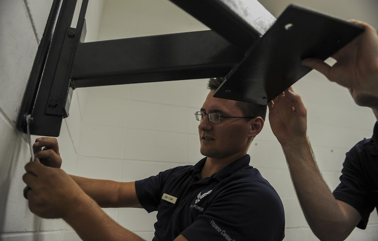 Senior Airman Robert Stark, a fitness specialist with the 1st Special Operations Force Support Squadron, sets up a speed bag in the Aderholt Fitness Center at Hurlburt Field, Fla., Oct. 11, 2016.  Fitness specialists receive one week of training in tech school solely based on fitness and receive on the job training once assigned to a fitness center. (U.S. Air Force photo by Airman 1st Class Isaac O. Guest IV)