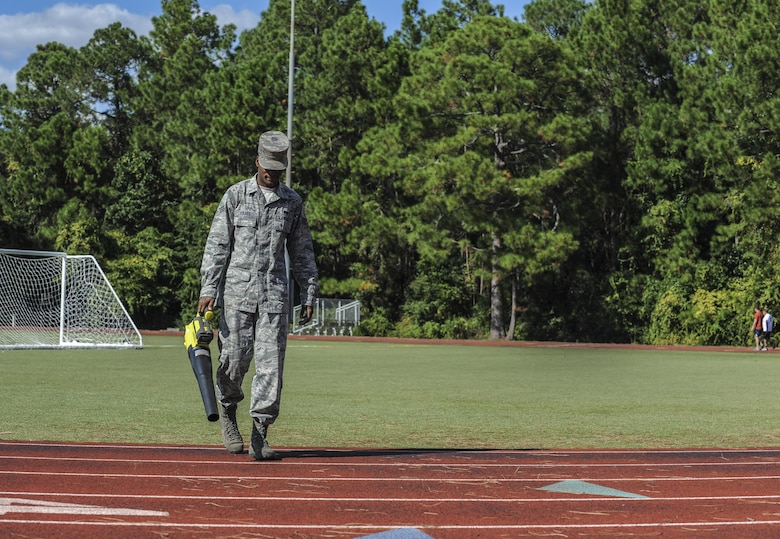Senior Airman Rycardo Folkes, an assistant sports director with the 1st Special Operations Force Support Sqaudron, blows away debris on the track behind the Aderholt Fitness Center at Hurlburt Field, Fla., Oct. 12, 2016. An assistant sports director's job includes guiding coaches and facilitating intermural sporting events. (U.S. Air Force photo by Airman 1st Class Isaac O. Guest IV)