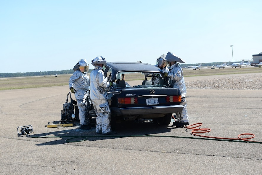 Firefighters use their tools to perform a vehicle extrication by removing the roof of a sedan Oct. 8, 2016, during the Fire Prevention Week open house at Columbus Air Force Base, Mississippi. Rather than remove the injured from the vehicle, firefighters are trained to remove the vehicle from the injured victim. (U.S. Air Force photo by Airman 1st Class John Day)