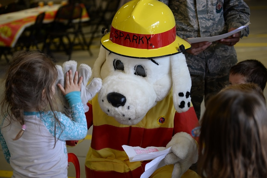 Sparky the Firedog gives a high five to a child Oct. 10, 2016, during Fire Prevention Week at Columbus Air Force Base, Mississippi. The children in attendance celebrated Sparky's 94th birthday at the party with games and more. (U.S. Air Force photo by Airman 1st Class John Day)
