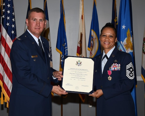 Col. James Fisher, 14th Flying Training Wing Vice Commander, hands Chief Master Sgt. Rita Felton, 14th Flying Training Wing Command Chief, her Certificate of Retirement Oct. 7 at Columbus Air Force Base, Mississippi. Felton served in the military for 30 years before joining her husband Derk Felton in retirement. (U.S. Air Force photo by Sharon Ybarra)